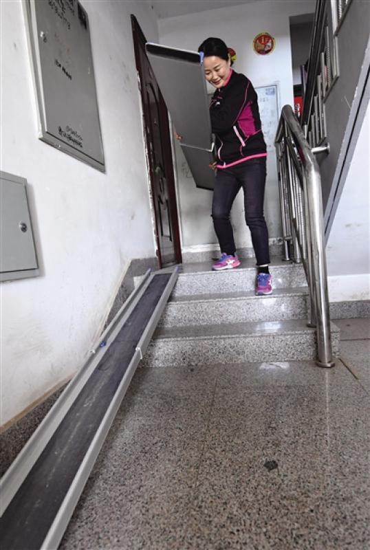 母親在樓道裏鋪設輪椅專用的軌道