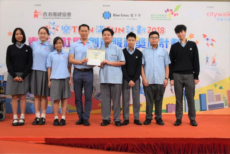 藍十字(亞太)保險有限公司執行董事尹志德先生頒發「樂TEEN滿FUN計劃2018」《青年x社區》創意服務獎勵計劃初級組金獎予林大輝中學學生組成的「大輝遊樂團」。