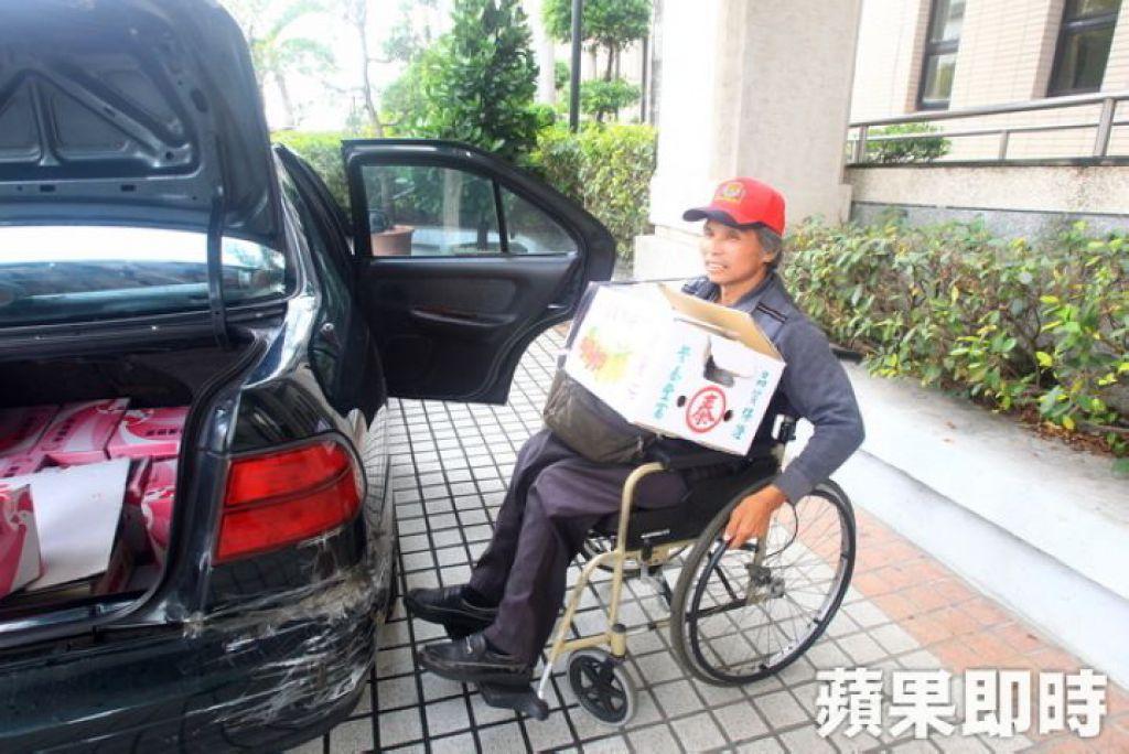 虽然双腿瘫痪,王永顺仍推著轮椅搬水果送货