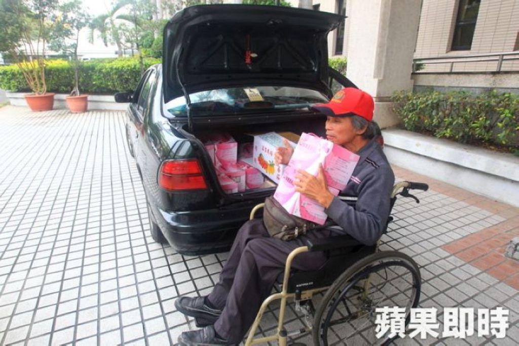 王永順推著輪椅用下巴頂住雞蛋送貨