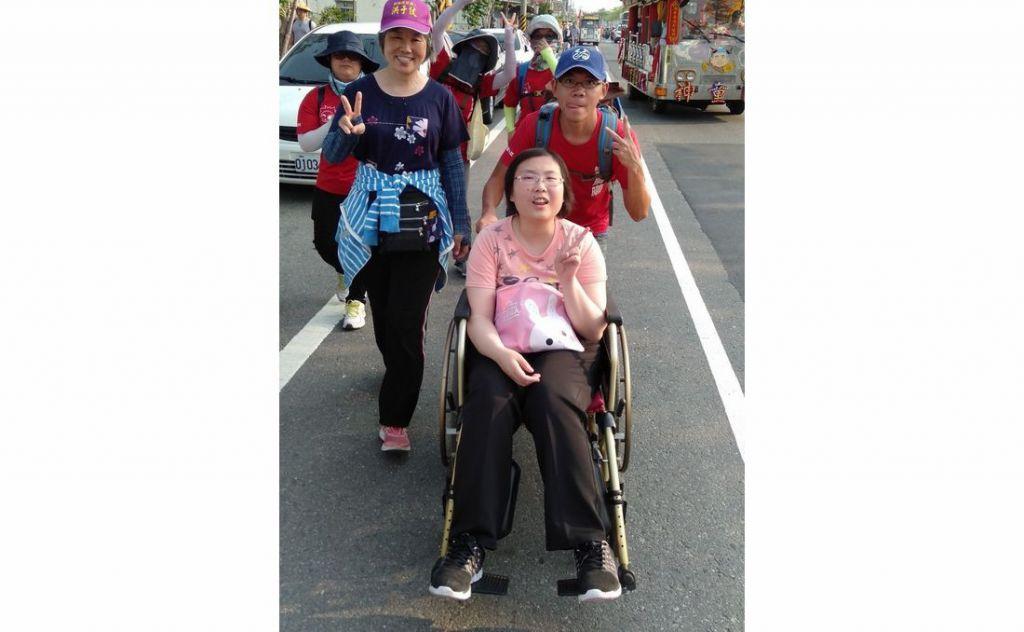 中州科技大學身障學生練姿足(前)在學校晨曦服務社志工協助下,開心完成參加大甲媽遶境祈福活動的心願