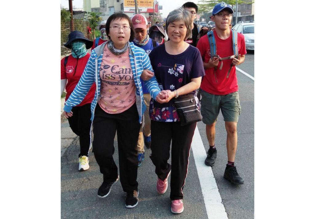 中州科技大學身障學生練姿足(左1)在媽媽陪伴下,勇敢離開輪椅,走了100公尺完成體驗大甲媽遶境祈福活動,讓師生和媽祖信眾感動