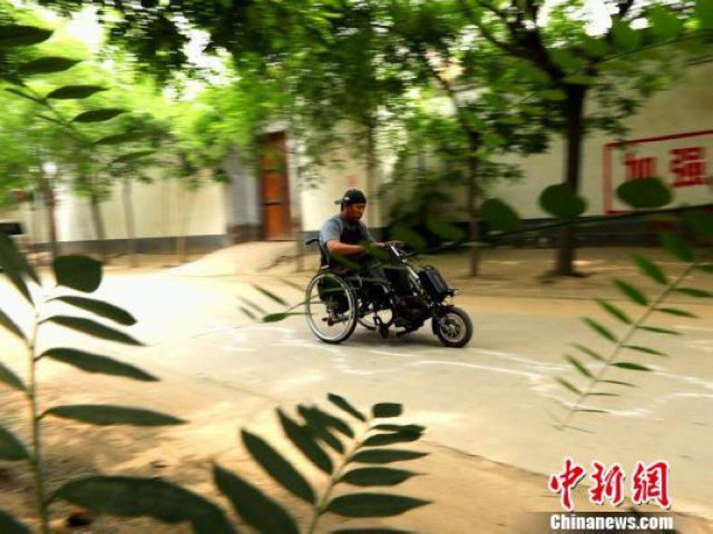 閆西博正在村內道路上測試他發明的輪椅車頭性能