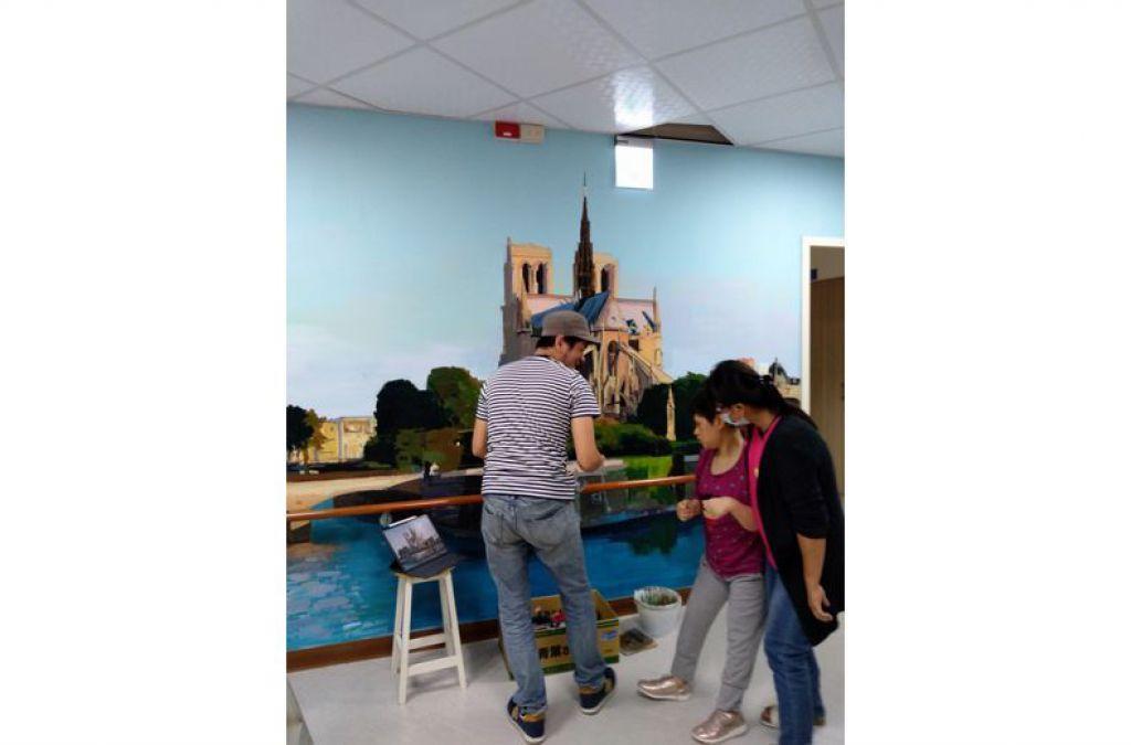 澎湖畫家許景翔2個月來當起「空中飛人」,為世光教養院的每個樓層彩繪廊道,院生好奇觀看。