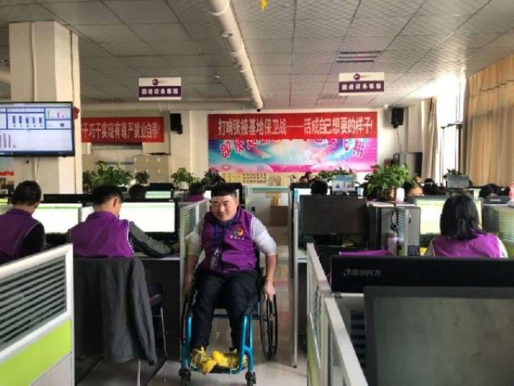 唐小鵬搖動輪椅走向自己的工位