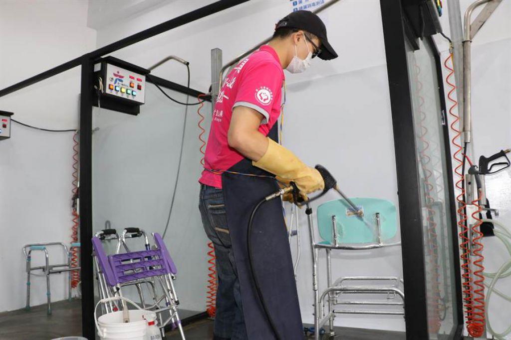 工作人員使用高壓噴槍清洗回收的二手輔具