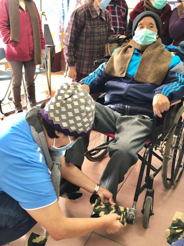 市議員陳昆和到禮化社區肯定理事長李黃麗敏有創意,輪椅踏板保護腳部也穿上襪子。