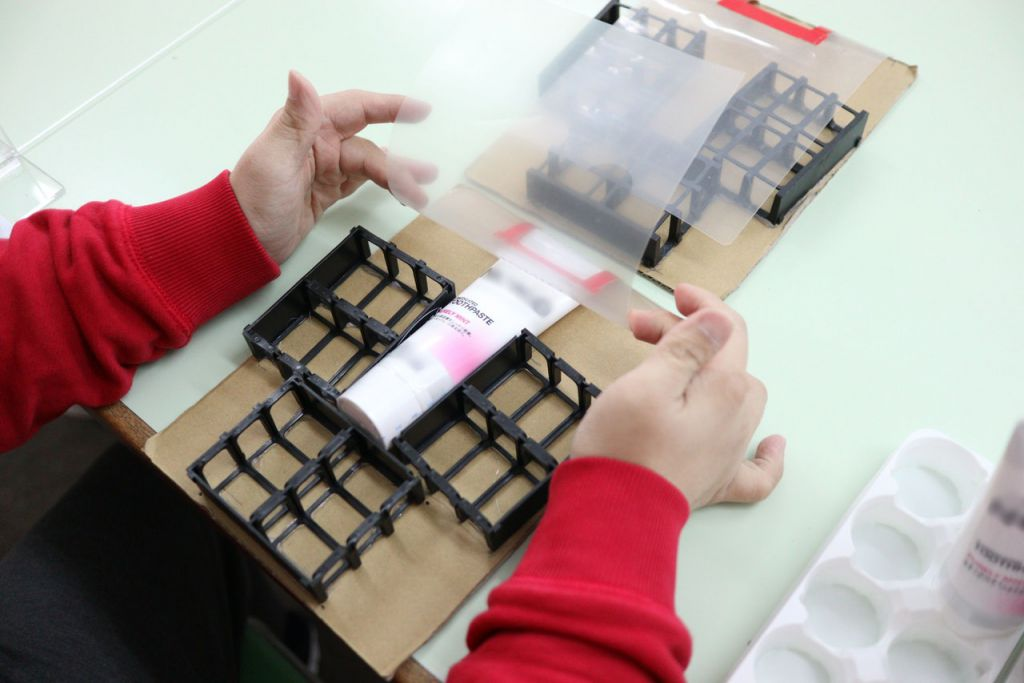 康復服務單位導師利用貨品廢料設計小工具,讓學員更容易把標籤貼到正確位置。