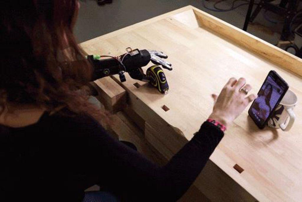 被試使用智能手機的手部追踪來編程的假肢夾點,以拿起捲尺並用另一隻手測量。