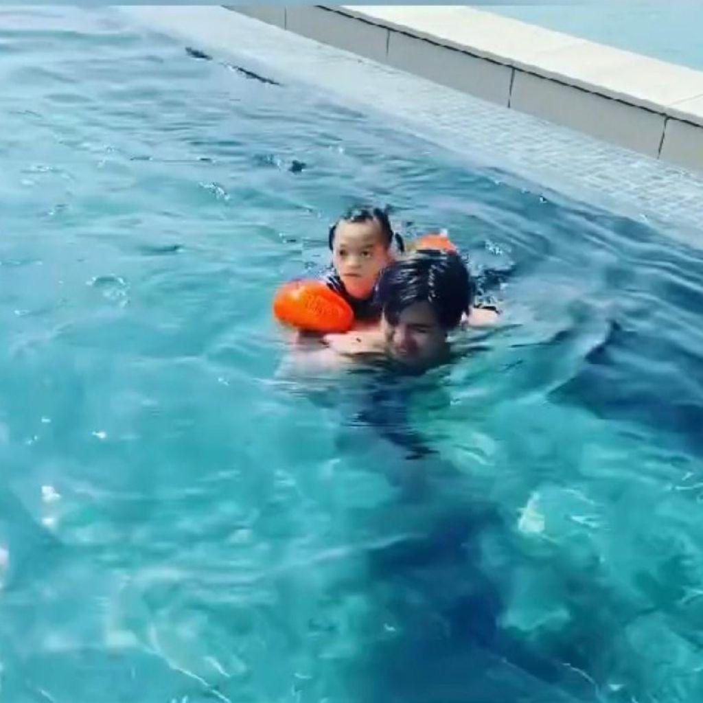 爸爸揹著Isabella游泳。